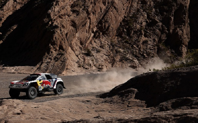 RIVER BEDS A PROBLEM: Stephane Peterhansel and his Peugeot tangled with a biker in a maze of tracks. Image: Dakar